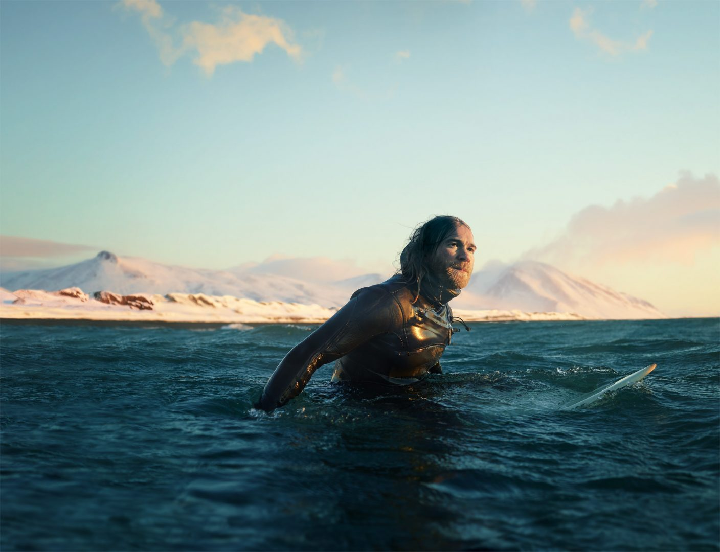 man surfing at sunrise in iceland with snowy mountains in background photo by Todd Antony