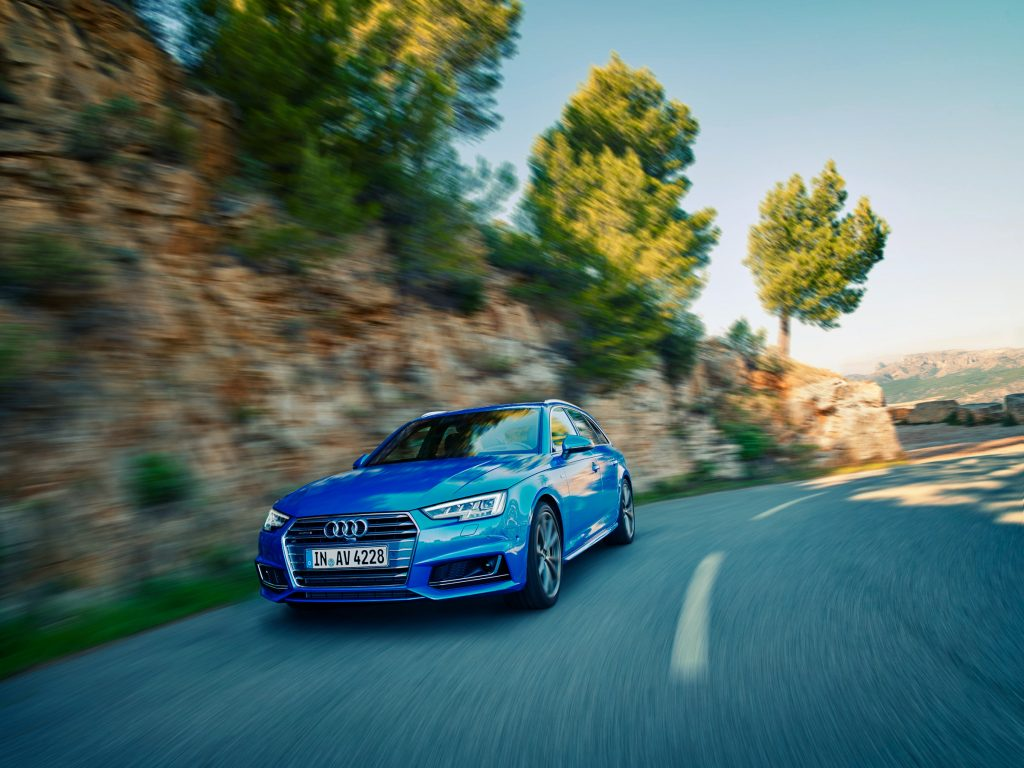 Blue Audi car driving up mountain road photo by Todd Antony