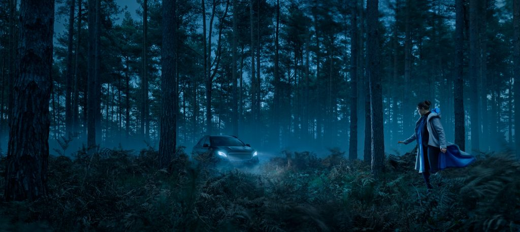 car in forest with headlights on horror movie feel photo by Todd Antony