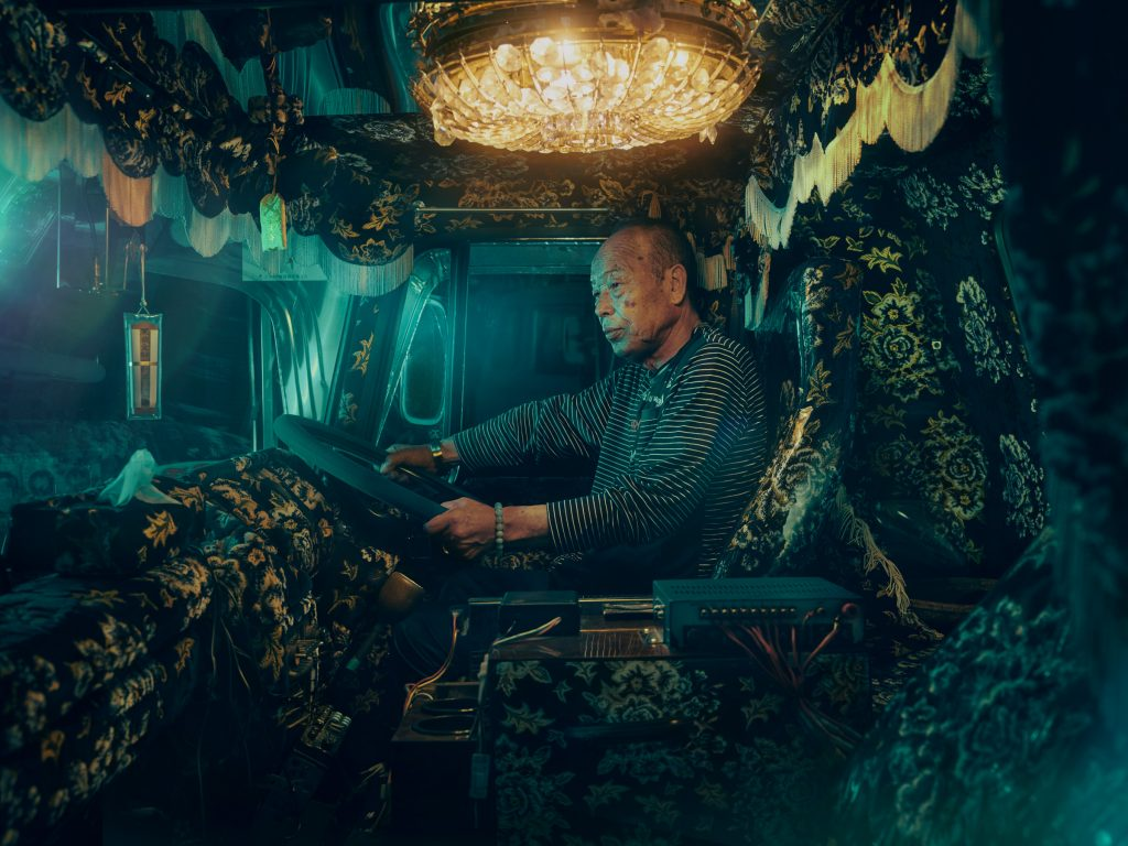 Japanese truck driver in the cab of his brightly decorated truck photo by Todd Antony