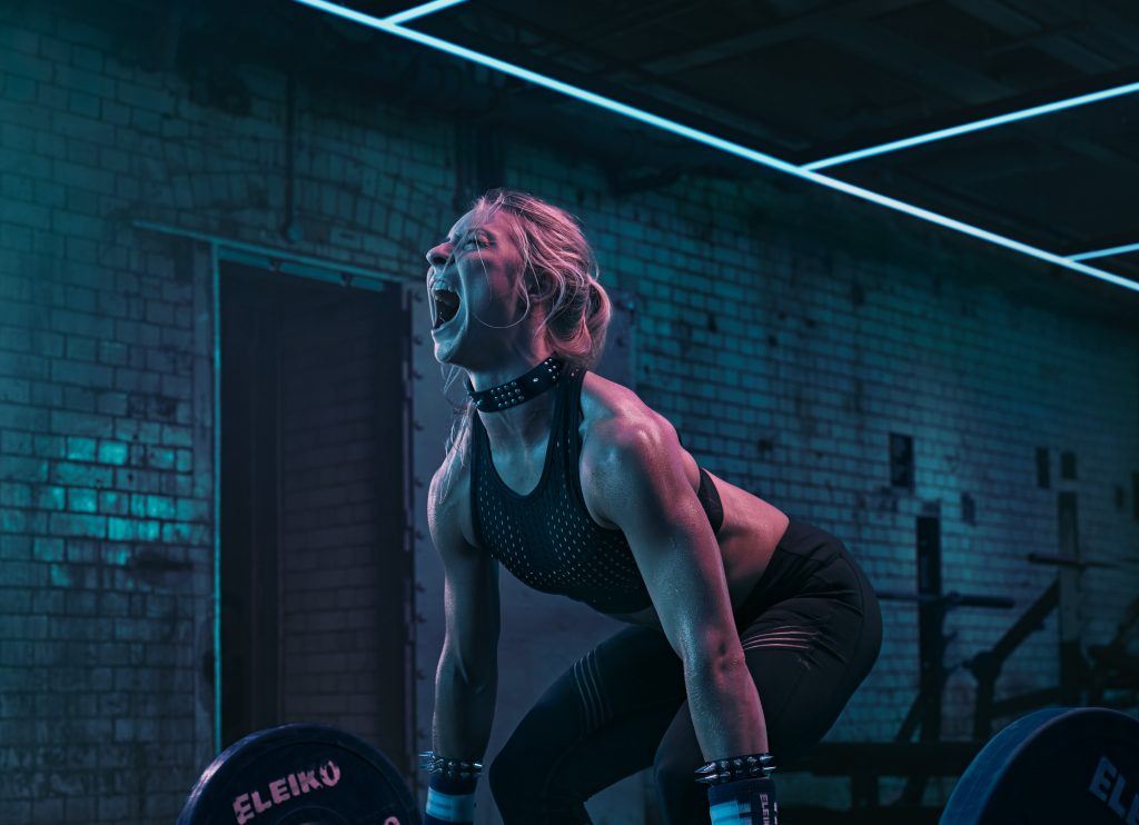 woman lifting weights in gym with coloured lighting photo by Todd Antony