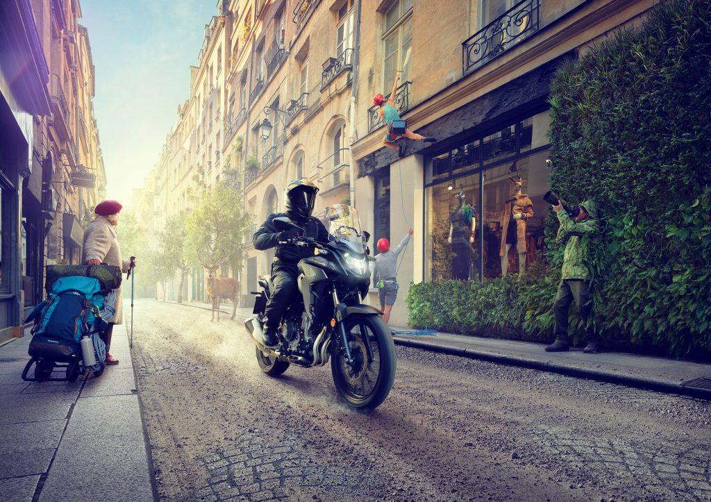 honda motorbike driving down city road in Paris photo by Todd Antony