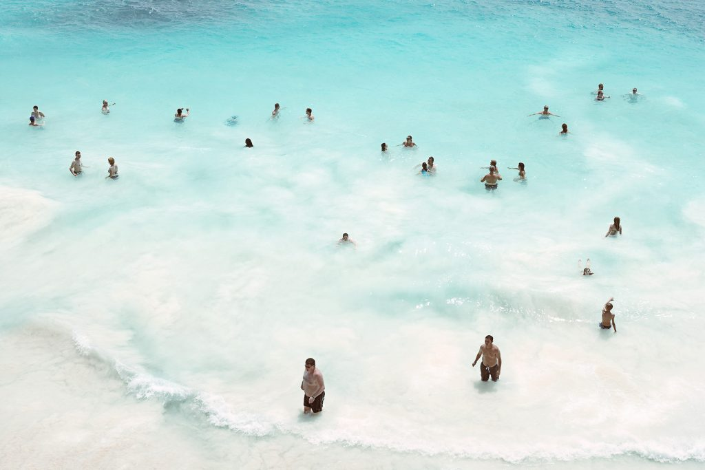people swimming in turquoise water at Tulum beach in Mexico photo by Todd Antony