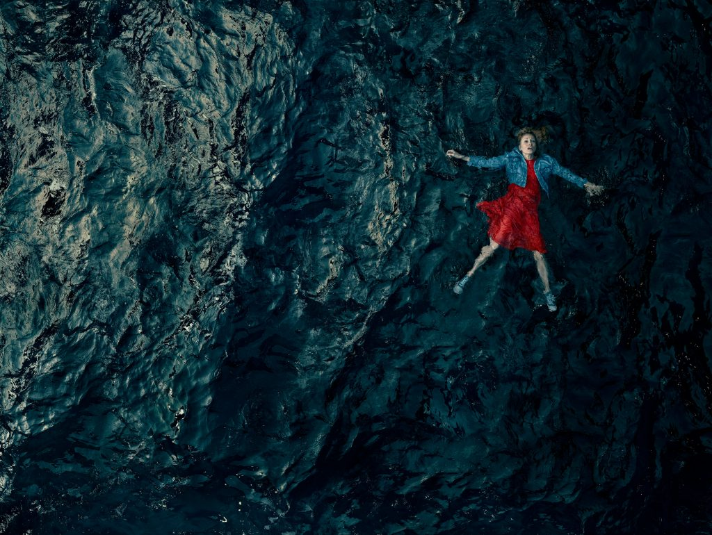 aerial view of woman floating in dark water with red dress on photo by Todd Antony RNLI