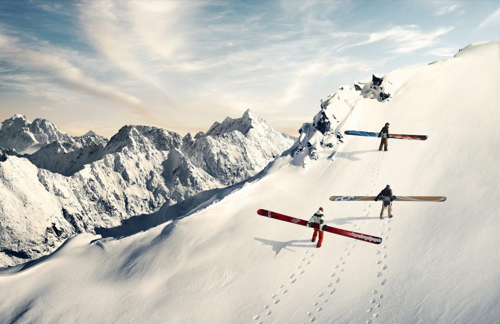skiers climbing up snowy mountain with very long snowboards photo by Todd Antony
