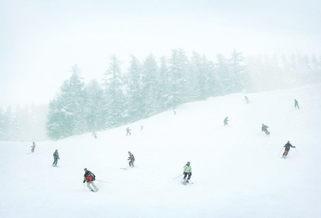 skiers on mountain on snowy day photo by Todd Antony
