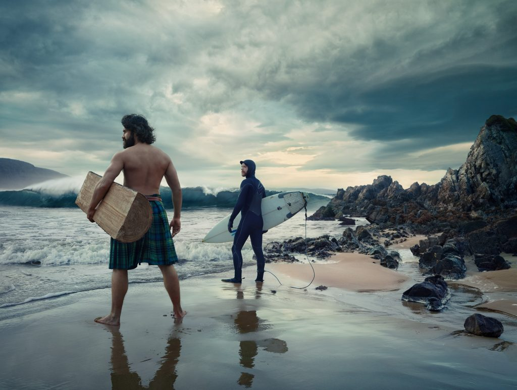 man wearing kilt and surfer on beach in Scotland photo by Todd Antony